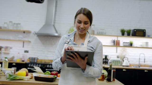 vídeos de stock, filmes e b-roll de linda jovem olhando receitas online usando um tablet em sua cozinha de casa sorrindo - receita