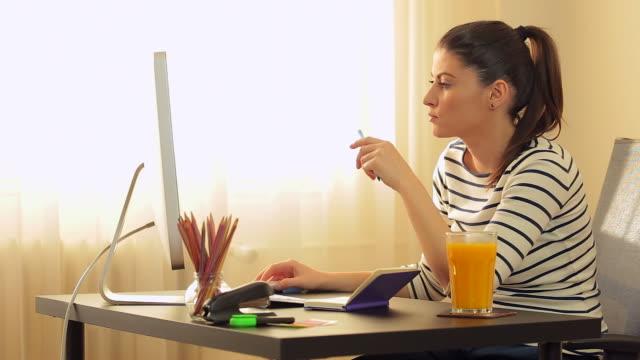 Mooie jonge vrouw op zoek naar monitor van de computer.