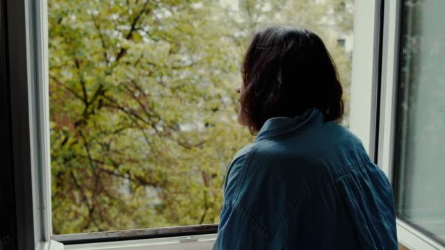 vídeos y material grabado en eventos de stock de beautiful young woman looking out of the window at street from old apartment building in berlin, germany. - mirar por la ventana