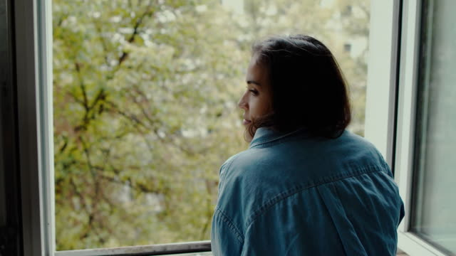 Beautiful young woman looking out of the window at street from old apartment building in Berlin, Germany.