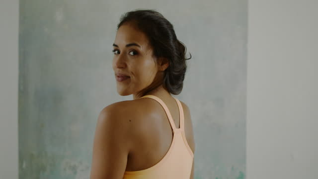 vidéos et rushes de beautiful young woman looking over shoulder, smiling, practicing yoga in bedroom in typical old berlin apartment building with wood floors and high ceiling in berlin, germany. - vêtement de sport