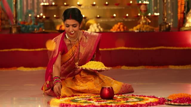 MS Beautiful young woman making a rangoli with flower petals during Ganesh Chaturthi / New Delhi, Delhi, India