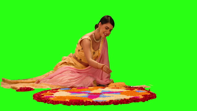 MS Beautiful young woman making a rangoli with flower petals during Diwali festival