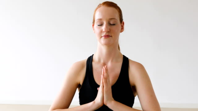 Beautiful young woman meditating in yoga class