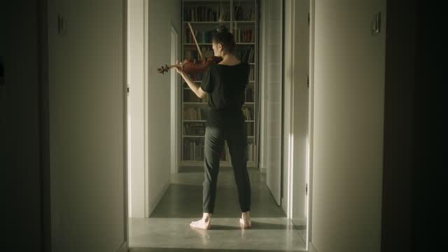 廊下でバイオリンを演奏する美しい若い女性ミュージシャン - バイオリン奏者点の映像素材/bロール