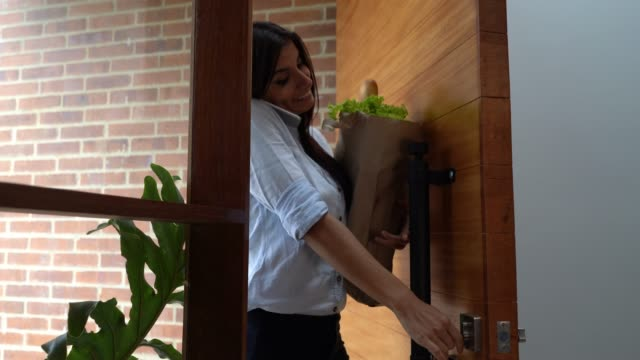 beautiful young woman opening door while talking on phone and carrying groceries - carrying stock videos & royalty-free footage