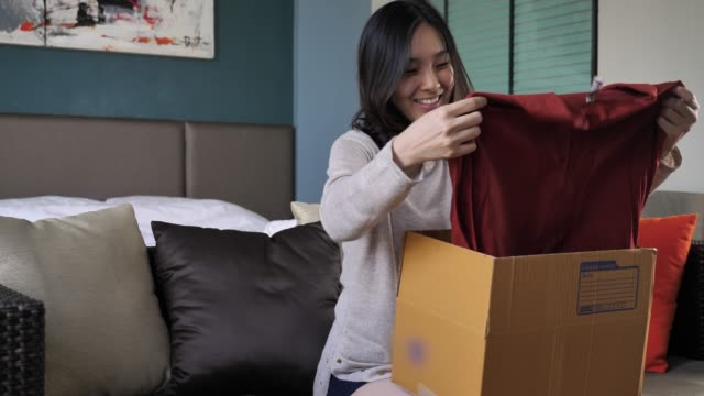 beautiful young woman opens cardboard box at home - parcel stock videos & royalty-free footage