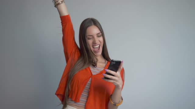 beautiful young woman overwhelmed with excitement while face-timing with friends. - punching the air stock videos & royalty-free footage