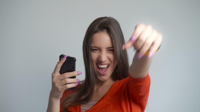 vídeos y material grabado en eventos de stock de hermosa joven abrumada de emoción mientras que la cara-timing con amigos. - premio