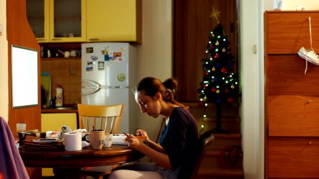 beautiful young woman painting in christmas atmosphere - oil paint stock videos and b-roll footage