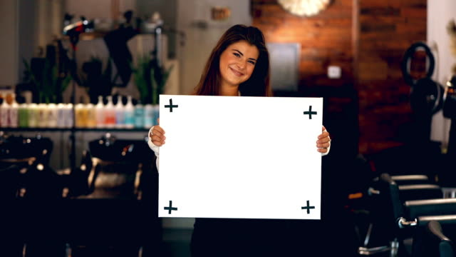 vidéos et rushes de belle jeune femme ramasse et retient le signe blanc blanc blanc dans le salon de coiffure à la mode - signalisation