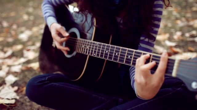 stockvideo's en b-roll-footage met beautiful young woman play guitar - cross processen