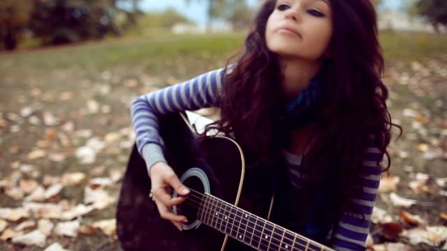 Schöne Junge Frau spielt Gitarre