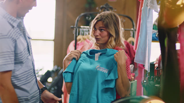 vídeos de stock e filmes b-roll de slomo. beautiful young woman playfully holds up graphic t-short for boyfrend whie looking through a gift shop at a winery. - loja de roupa