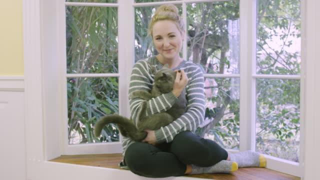 vídeos y material grabado en eventos de stock de hermosa mujer joven tocando y abrazando con su gato en el interior - pijama
