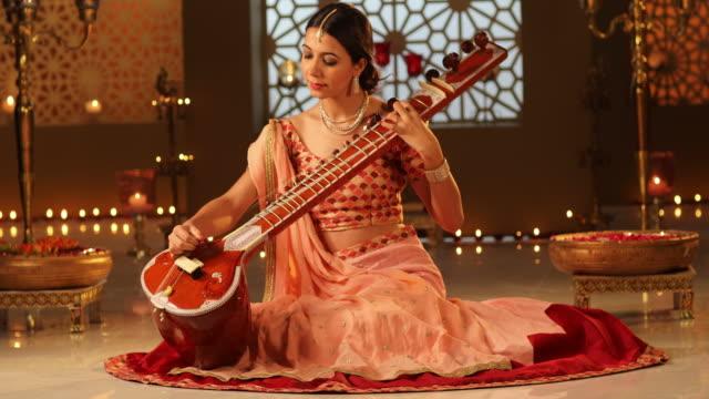 MS Beautiful young woman playing sitar during Diwali festival / New Delhi, Delhi, India