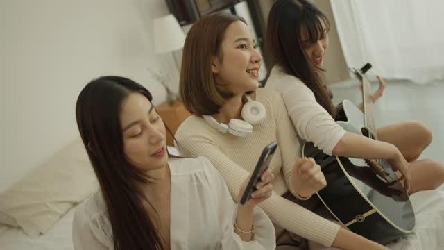 vidéos et rushes de la belle jeune femme joue la guitare avec des amis - singer