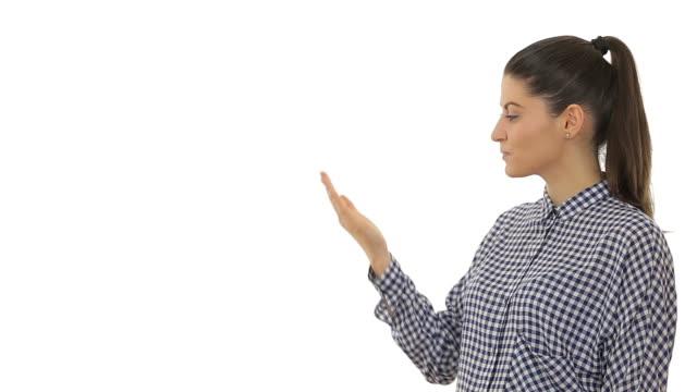 Bela Jovem mulher a apontar com cópia espaço e mostrando Sinal de Okey.