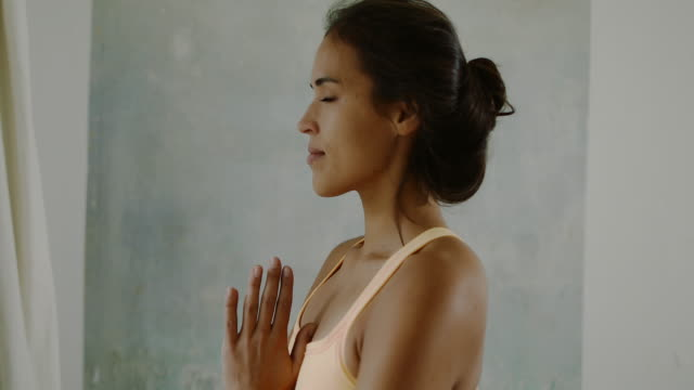 Beautiful young woman practicing yoga with closed eyes, breathing in bedroom in typical old Berlin apartment building with wood floors and high ceiling in Berlin, Germany.