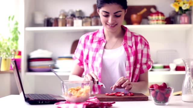 Schöne junge Frau, die Zubereitung von gesunden Frühstück