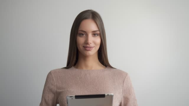 beautiful young woman presenting while holding digital device. - model object stock videos & royalty-free footage