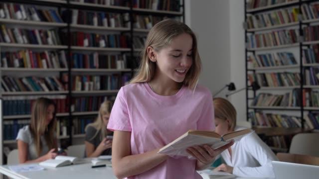 Schöne junge Frau, die ein Buch lächelnd liest, während andere Studenten im Hintergrund in der Bibliothek sind