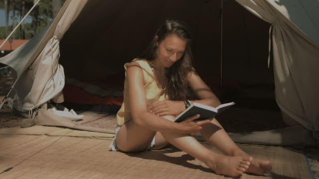 beautiful young woman reading book in front of tent in sunshine at atlantic coast in south of france in summer - camping stock videos & royalty-free footage