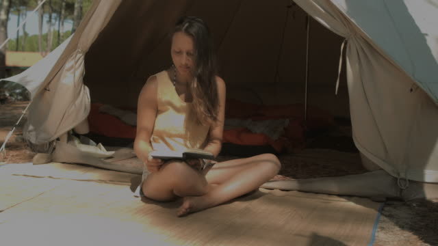 Beautiful young woman reading book in front of tent in sunshine at Atlantic coast in South of France in summer