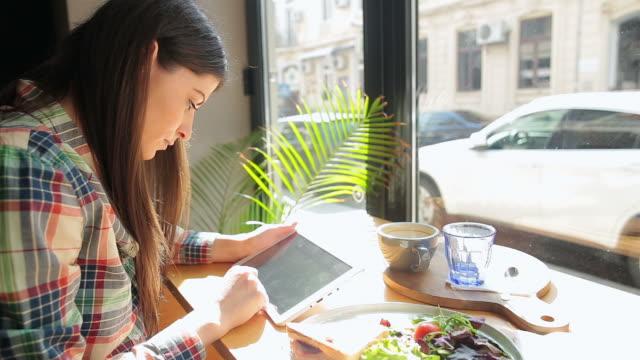stockvideo's en b-roll-footage met mooie jonge vrouw lezen op de tablet pc in de winkel van de koffie. - sunny