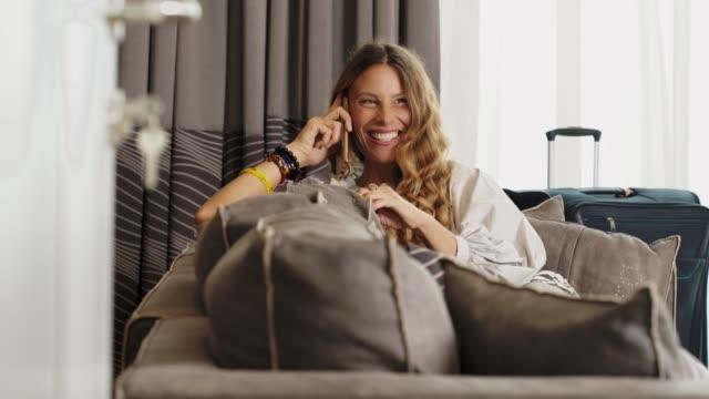 vídeos de stock, filmes e b-roll de mulher nova bonita que relaxa em um hotel de luxo usando um smartphone. - viagem de negócios