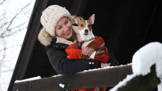 beautiful young woman relaxing on winter vacation with her dog - casacca video stock e b–roll