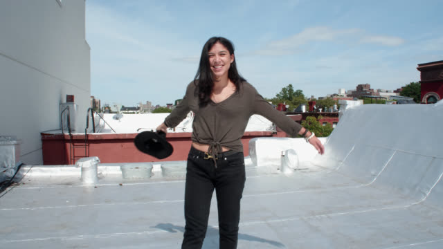 beautiful young woman removes hat and spins excitedly for camera on city rooftop - nose piercing stock videos & royalty-free footage