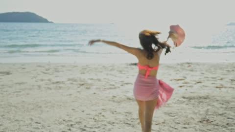 浜辺の海の水に走っている美しい若い女性 - ほっそりした点の映像素材/bロール