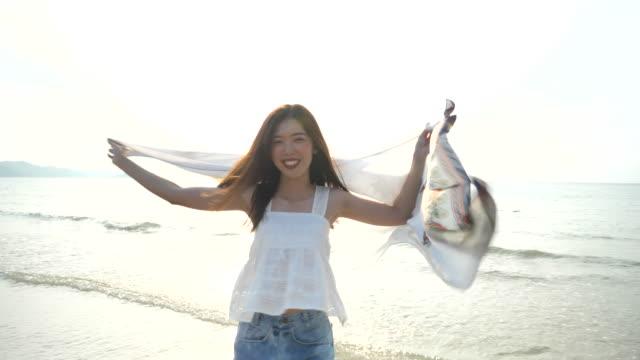 schöne junge frau läuft ins meerwasser am strand - only young women stock-videos und b-roll-filmmaterial