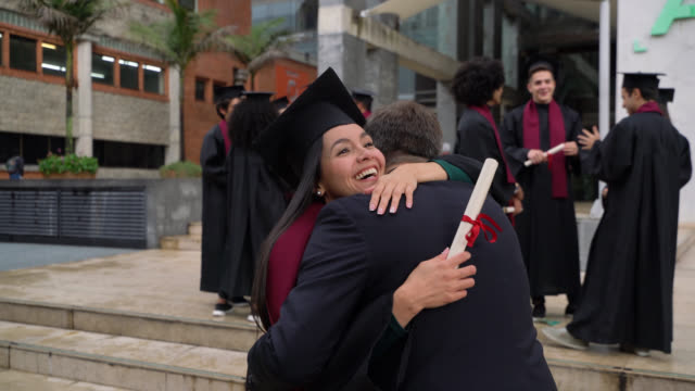 beautiful young woman running towards her father to hug him after graduation ceremony - diploma stock videos & royalty-free footage