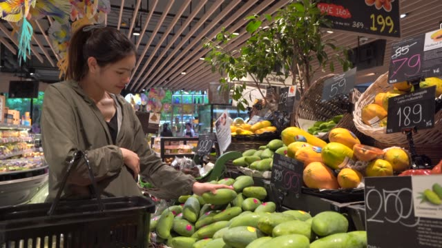 beautiful young woman shopping for fruits and vegetables in produce department - papaya stock videos & royalty-free footage