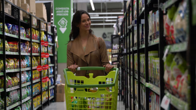 beautiful young woman shopping for groceries and looking at products on shelf while pushing cart - cart stock videos & royalty-free footage