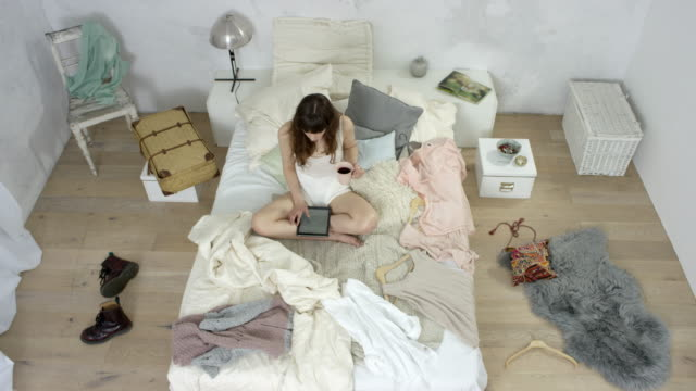 vidéos et rushes de beautiful young woman - sits in bed with cup of coffee and uses ipad - messy bedroom