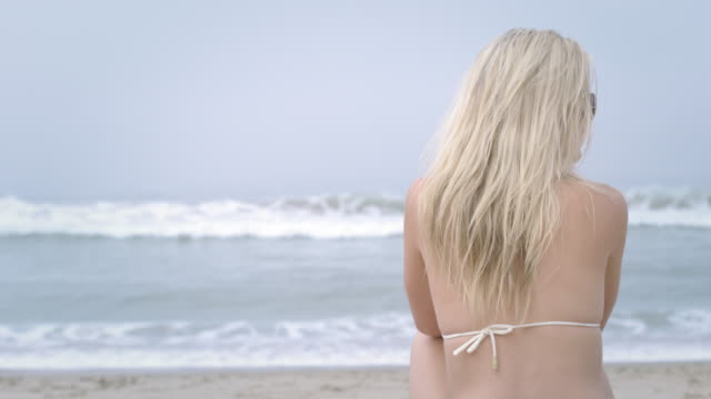 beautiful young woman sits on beach watching the ocean 4k - vesper stock stock videos & royalty-free footage