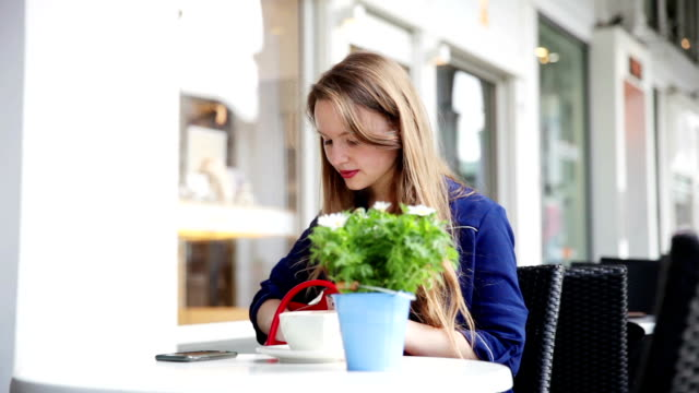 Beautiful young woman sitting in a outdoor cafe