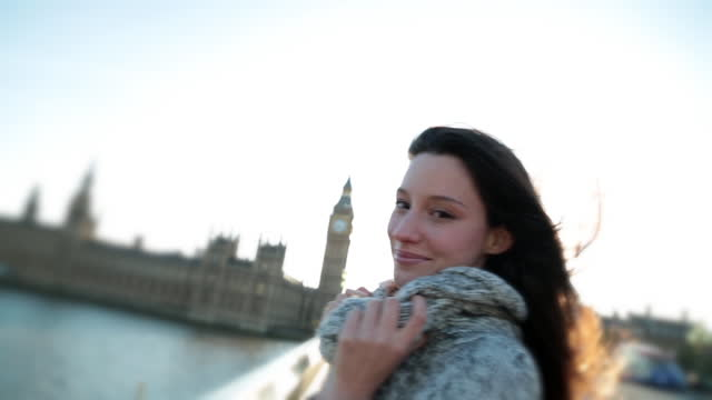 beautiful young woman smiles and poses for camera on westminster bridge. - jumper stock videos and b-roll footage