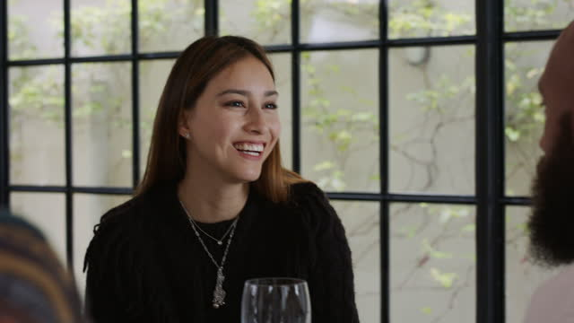 beautiful young woman smiling and talking at dinner - brown hair stock videos & royalty-free footage