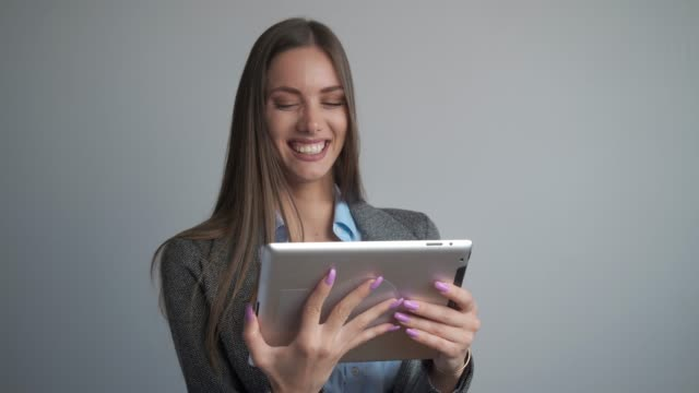 beautiful young woman smiling at the camera holding a digital tablet. - only young women stock videos & royalty-free footage
