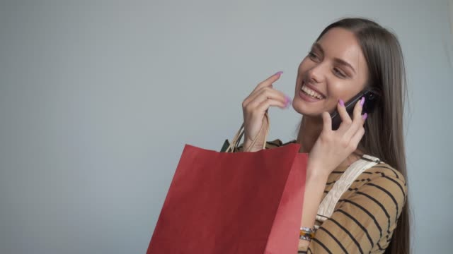 beautiful young woman smiling at the camera holding a shopping bags and smart phone. - only young women stock videos & royalty-free footage