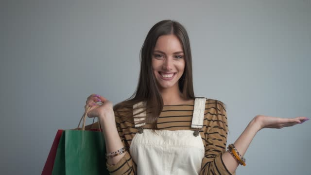 beautiful young woman smiling at the camera holding a shopping bags. - only young women stock videos & royalty-free footage