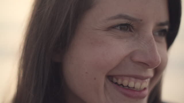 cu beautiful young woman smiling outdoors - lachen stock-videos und b-roll-filmmaterial