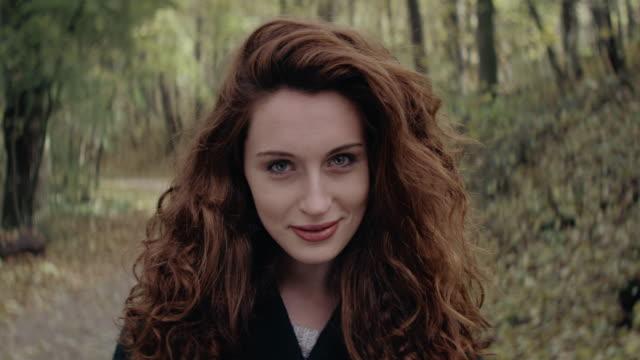 Schöne junge Frau stehend und Lächeln im Wald