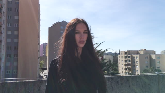 beautiful young woman standing on city street outdoors - part of a series stock videos & royalty-free footage
