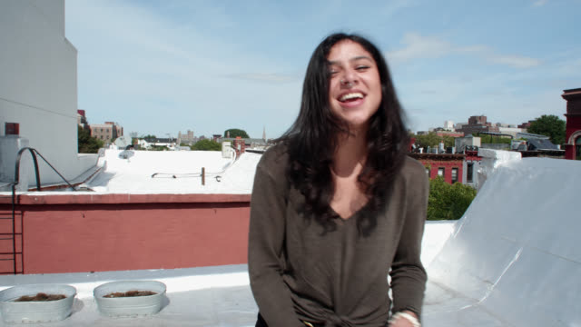 beautiful young woman struts and points hat at camera on city rooftop - nose piercing stock videos & royalty-free footage