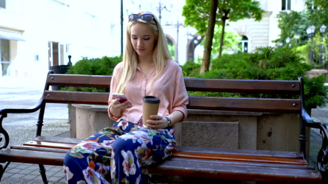 Beautiful young woman talking on her phone and sitting outdoors at the bench
